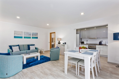 Elegant open plan lounge & dining area with Kitchen in the background all in shades of blue.