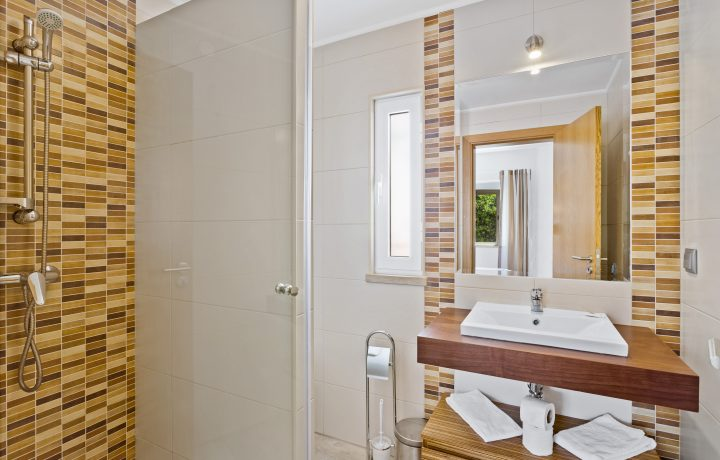 on-suite bathroom with shower, hand washer in browm colours